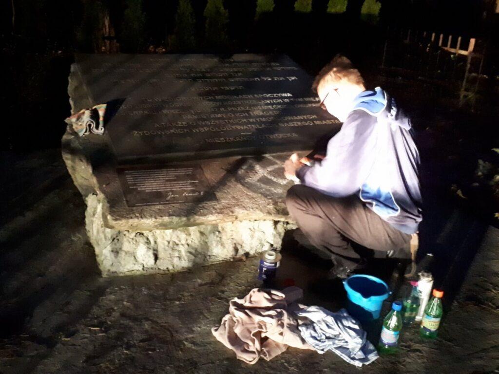 Czyszczenie swastyk na kamieniu pamięci Żydów otwockich. Fot. Więź