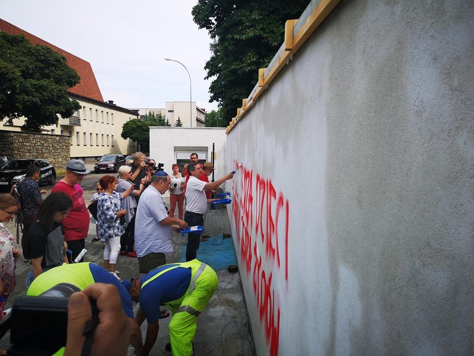 Mieszkańcy Tarnowa zamalowują antysemicki napis na murze żydowskiego cmentarza