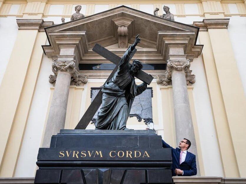 Premier Mateusz Morawiecki przy pomniku Chrystusa niosącego krzyż przed kościołem św. Krzyża